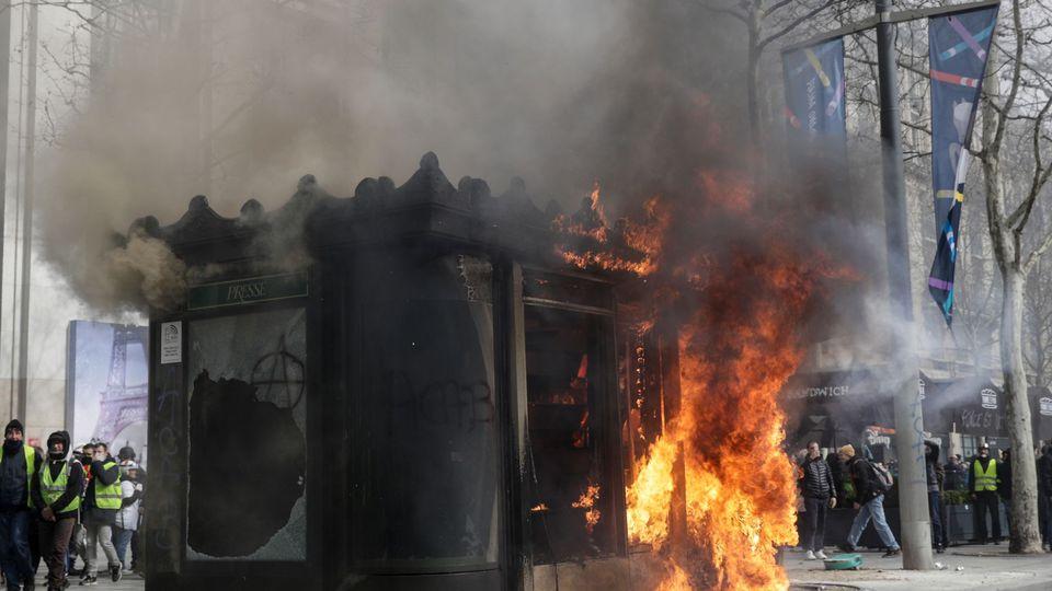 Les Cons de certains fwançais Kioske-a-journaux-en-flammes-sur-l-avenue-des-champs-elysees-lors-de-la-manifestation-des-gilets-jaunes-le-16-mars-a-paris_6162684